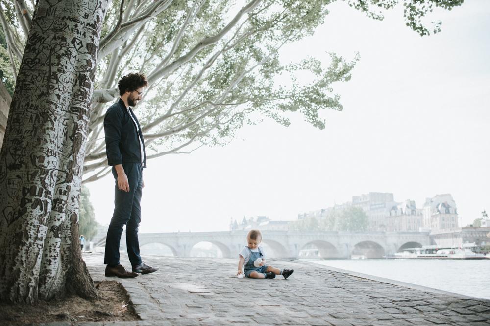 un papa est debout sur les quais de seine et regarde son bébé qui joue avec son biberon au sol