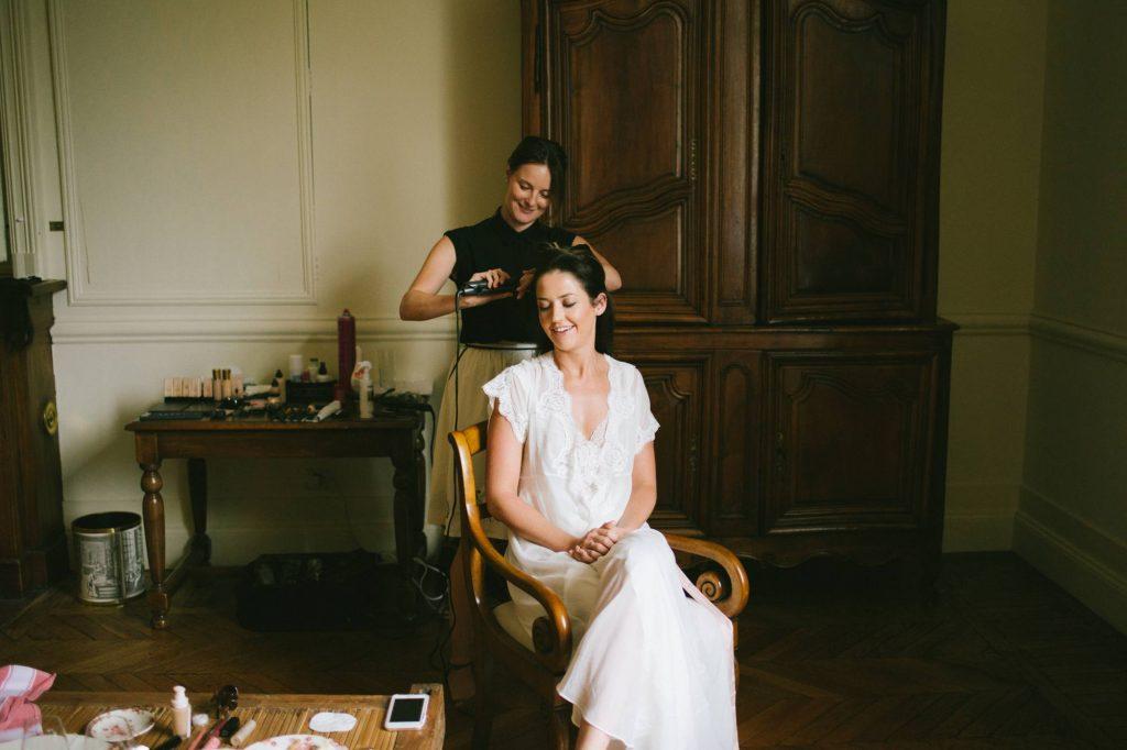 la mariée sourit pendant sa préparation avant le mariage
