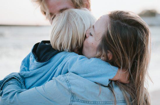 un papa et une maman tiennent dans leurs bras leur petit garçon, la maman lui fait un bisou, ils sont tous les 3 collés. C'est une lumière de fin de journée en bord de mer
